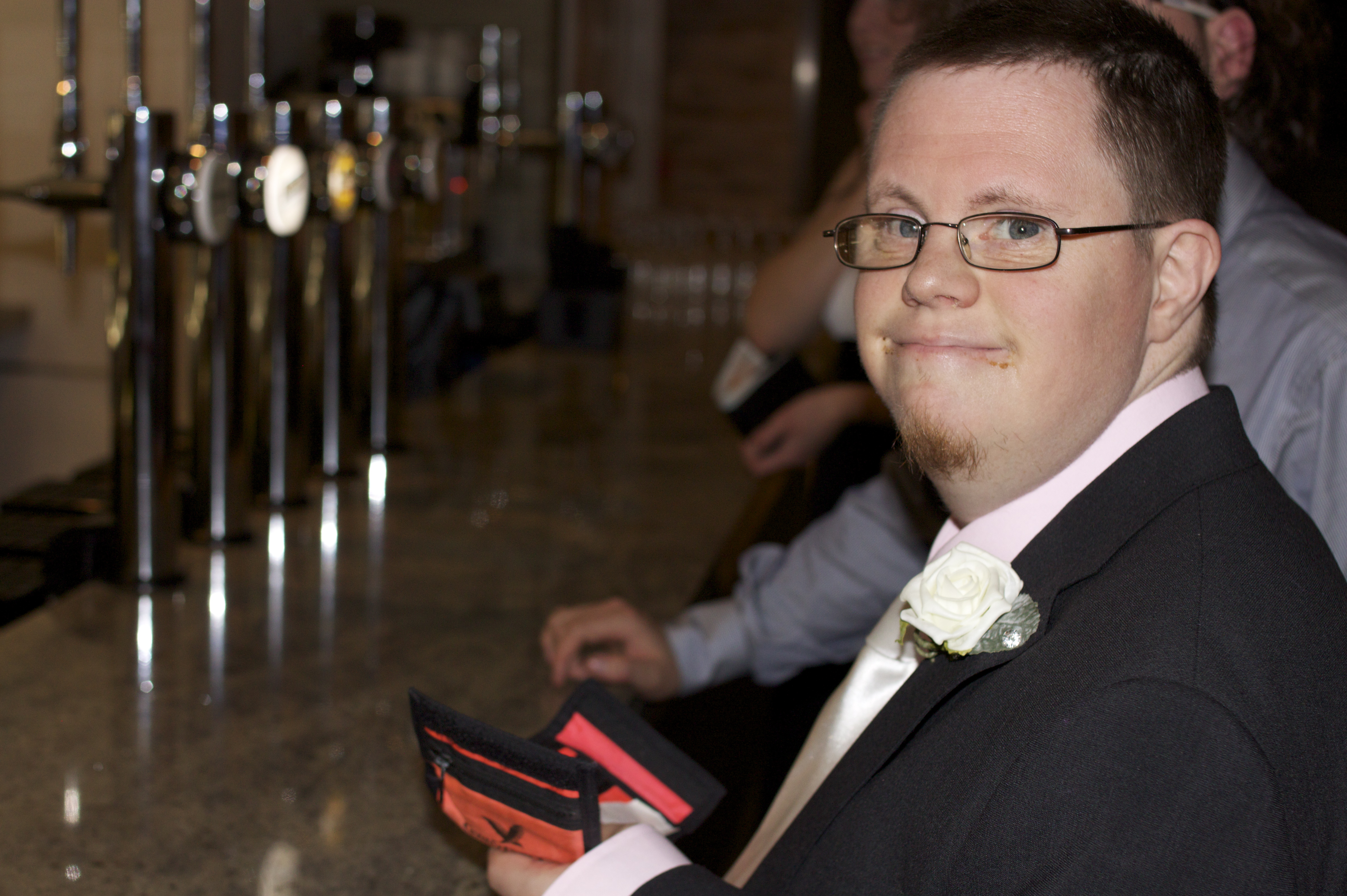 A young man in a suit stands at a bar holding his wallet, looking past the camera.